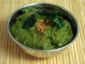 1. First you have to wash the coriander leaves thoroughly so that no sand is present and cut the leaves into pieces. 2. Then take green chilies and clean them too. 3. Now take a bowl, pour 3 tbsps of oil and let it heat 4. After the oil heats, add the green chili to the oil and fry them lightly. 5. After the chili is fried, transfer them to mixer jar, and add the coriander leaves to the bowl, and fry them too for two to three minutes. 6. Once the coriander leaves are done let them cool. 7. Now add the cooled leaves along with salt, little jeera, tamarind, garlic cloves, into a mixer jar and mix them lightly. 8. After the mixture is ready, take a bowl and add 2-3 tbsps of oil and let it heat. 9. After the oil is heated add the pulses (popuginjalu), garlic cloves, jeera, mustard, curry leaves, red chilies, turmeric powder and let them fry for a minute. 10. Add the coriander leaves mixture into the oil and mix them. 11. Your tasty and healthy kothimira pachadi is ready to taste.